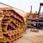 New track chain, employee working on Equipment in Yard